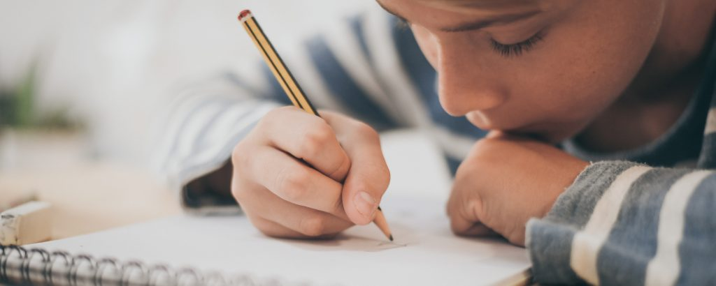 Student drawing with pencil on the notebook. Boy doing homework writing on a paper. Kid hold a pencil and draw a manga at home. Teen drawing sitting at the table. Education art talent ability concept.